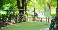Elegant  Beautiful woman in the park relaxing outdoors on a decorative bridge, - stock footage