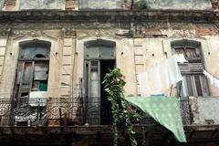 Havana, Cuba, balcony and facade of a house in a desolate condition - stock photo