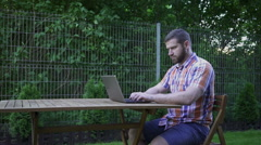 Man writing on a laptop, sitting on wood chair in small garden. Stock Footage