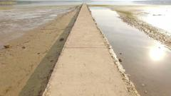 Fly over long boardwalk to the sea Stock Footage