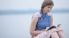 Girl reading a book by the river Stock Footage