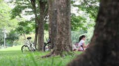 Young adults relaxing in central city park after rides bicycles, BANGKOK Stock Footage