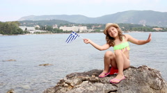 Happy little girl waving with greek flag on beach Corfu Greece Stock Footage