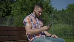 Man is sitting on wooden bench and browsing smartphone. Stock Footage