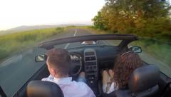 Attractive caucasian friends enjoying driving in sunshine in their open top car Stock Footage