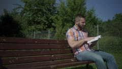 Man is reading a book on the wooden bench. Stock Footage