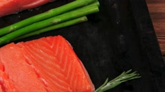 Fresh raw pink salmon on black tray with rosemary and asparagus Stock Footage