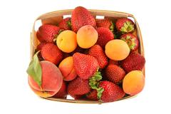 Strawberries, apricots and peach in wooden basket isolated on white - stock photo
