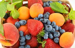 Strawberries, apricots, blueberries, peach and mint isolated on white - stock photo