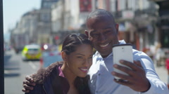 4k Happy attractive couple in the city taking a selfie with camera phone Stock Footage