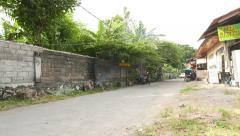 Backstreet in Kuta slum area, fire burns at grey brick wall Stock Footage