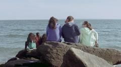 Kids On A Rock Talking In Front Of Atlantic Ocean in Brighton Beach New York Stock Footage