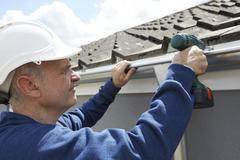 Stock Photo of Workman Replacing Guttering On Exterior Of House