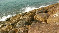 Wave breaker stones closeup, calm emerald-colored sea water splashe about rock Stock Footage