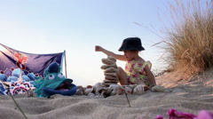 Little girl playing with sand and stones on the seashore, Model Release - stock footage