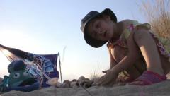 Little girl playing with sand on the seashore, Model Release - stock footage