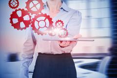 Stock Illustration of Composite image of businesswoman holding digital tablet