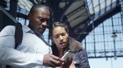 4k Attractive couple on train station platform using mobile phone for navigation Stock Footage