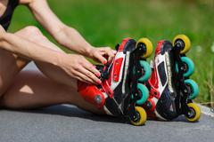 Young girl putting on inline skates - stock photo