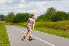 Attractive girl rollerblading on the road Stock Photos