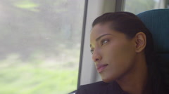 4k Beautiful woman relaxing and looking out of window on train journey Stock Footage