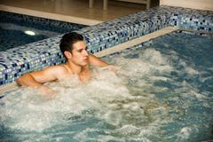 Young Man Relaxing in Spa Whirlpool - stock photo