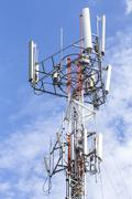 Cell Phone Tower with White Cloud and Blue Sky - stock photo