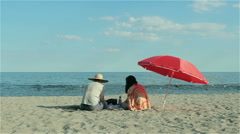 Two people sitting on the beach under red parasol Stock Footage