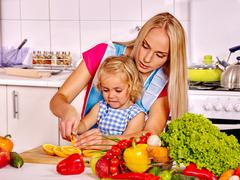 Mother and child cooking at kitchen - stock photo
