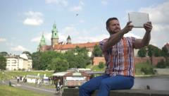 Man takes a selfie, sitting on the wall. Stock Footage