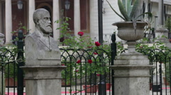 Statue and flower pot surrounding red flowers on fence Stock Footage