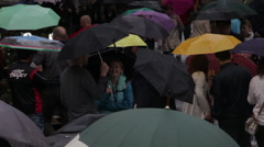 Strangers talk in a umbrella filled crowd Stock Footage