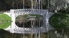 The small shabby bridge in park over a pond. Gatchina. Petersburg. Russia. - stock footage