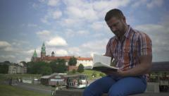 Man reading book on the wall by the river. Stock Footage