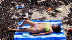 Model posing in polluted beach Stock Footage