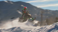 Snowmobile race with snowmobilers jumping. Stock Footage