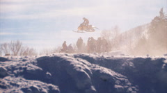 Clip of a snowmobile race with snowmobilers jumping. Stock Footage