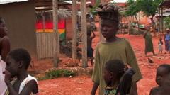 African boy carrying goods on his head in a village. Stock Footage