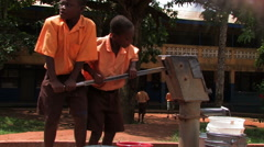 African boys pumping water from a well. Stock Footage