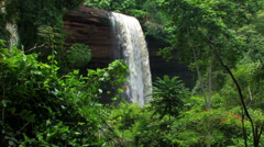 Waterfall from a cliff surrounded by greenery. - stock footage
