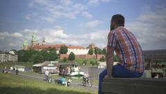 Man sitting on wall by the river Stock Footage