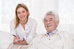 Care assistant and elder man - stock photo