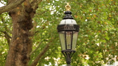 Close up of top of street light with green trees in background in London, Stock Footage