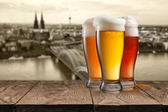 Glass of beer with view of Koeln on background - stock photo