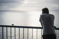 Caucasian man admiring ocean view from railing Stock Photos