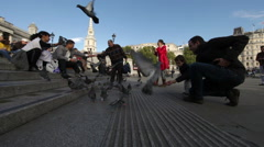 LONDON - OCTOBER 7: The shot pans as people feed pigeons on the Trafalgar Square Stock Footage