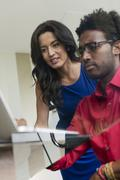 Hispanic business people using laptop at glass office desk Stock Photos