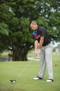 Caucasian man teeing off on golf course Stock Photos