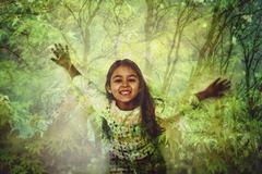 Mixed race girl standing in forest projection Stock Photos