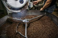 Caucasian roaster working on coffee in machinery Stock Photos